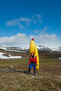 Lars Larsson bär kajaken över fjället till Sieldutjåhkå.